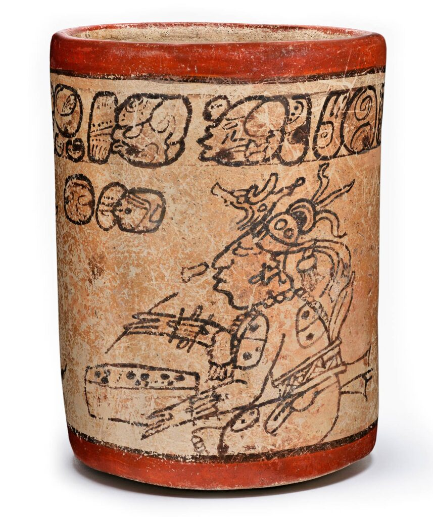 A cup illustration with symbols along the top, and a person seated with a tablet, wearing an elaborate headpiece.