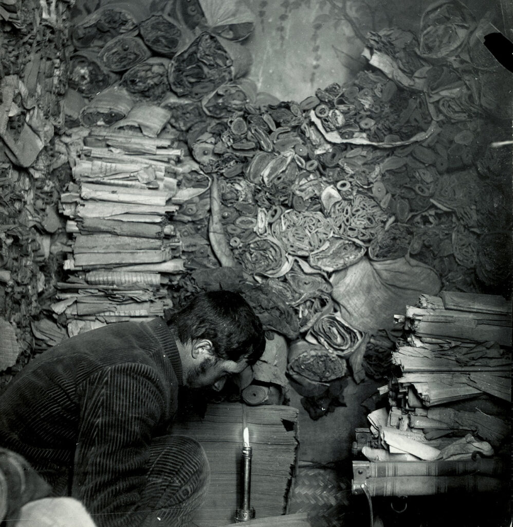 A man kneels by a candle, surrounded floor to ceiling by books and scrolls.