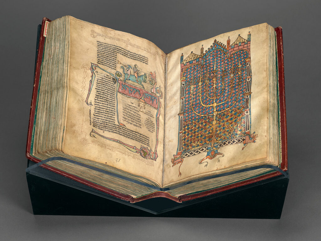 An old, bound book sits open on a pedestal. The left folio contains writing with illustrations of a knight on a horse. The right folio is an illustration of a candelabra backed by a stained glass building facade.