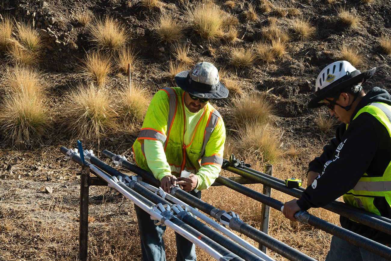 Two men in safety vests and hats working on pipes next to a hillside.