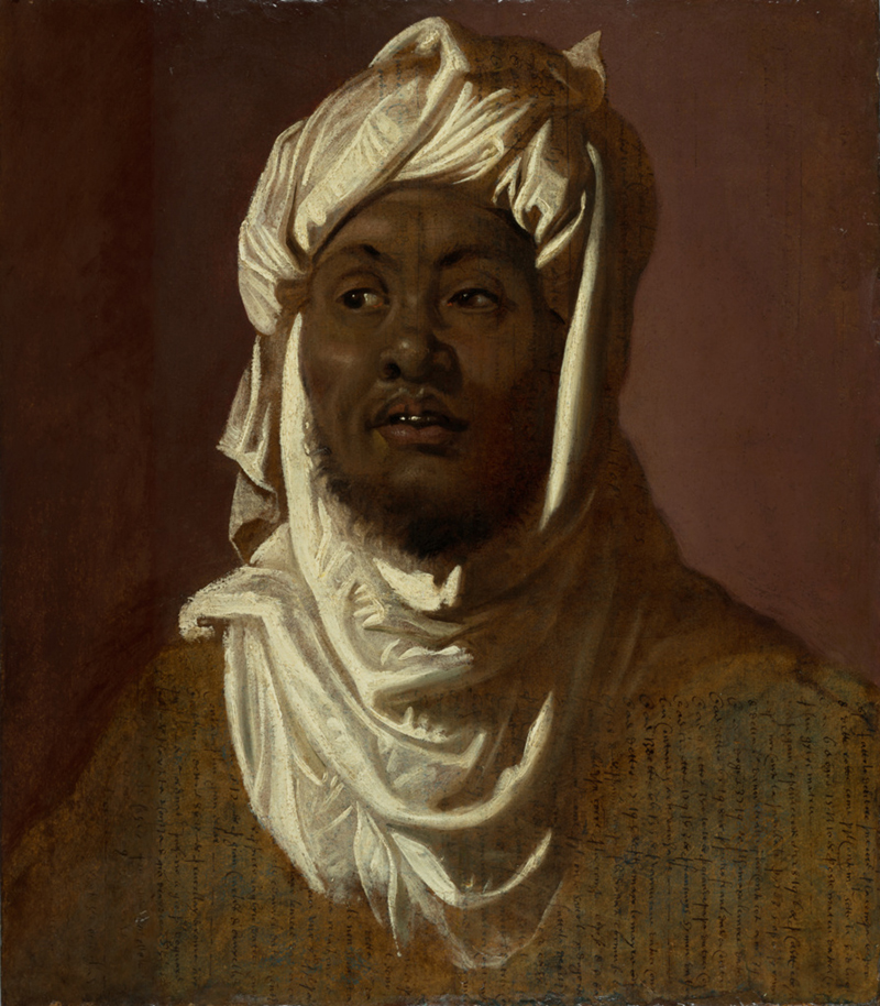 Head and shoulders of a black man with a short beard, wearing a white turban.