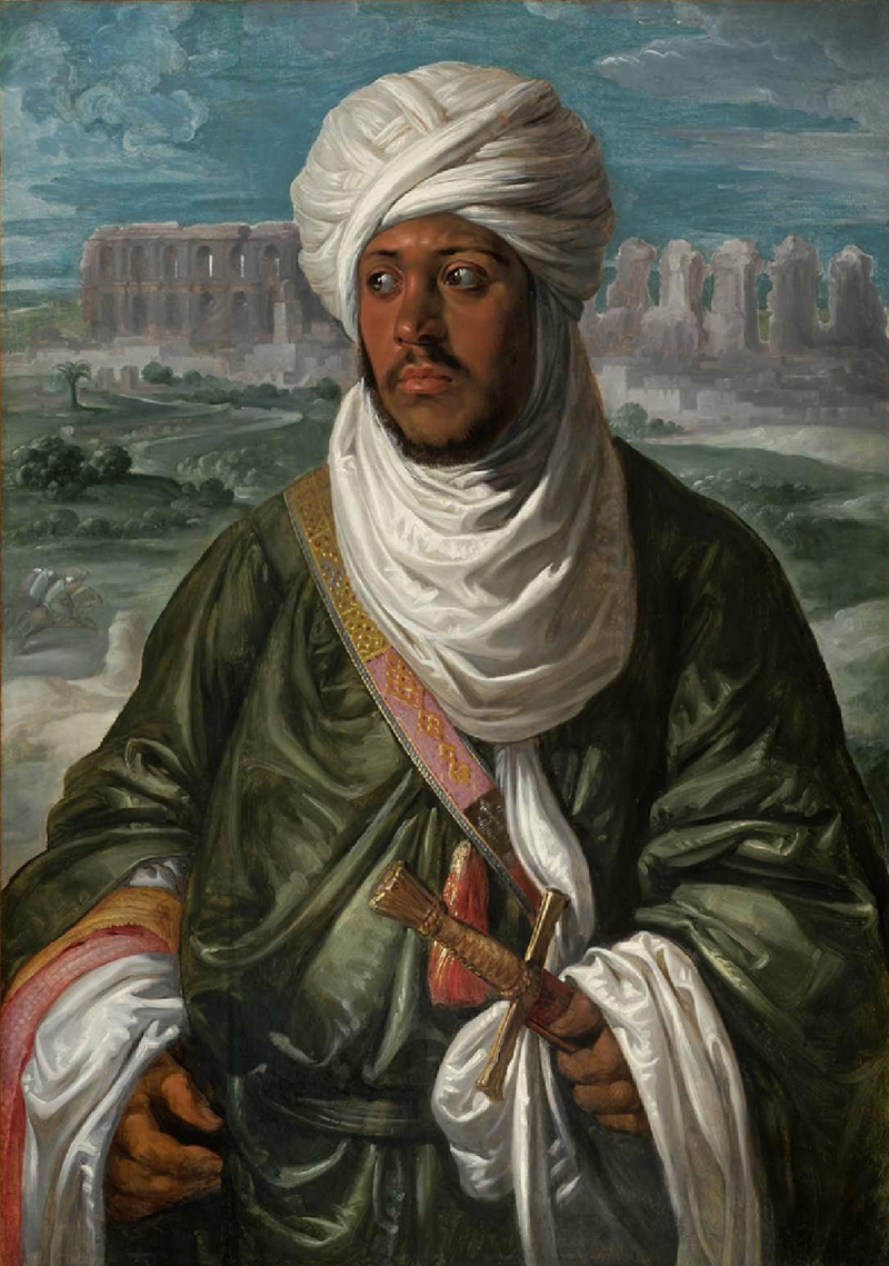 Upper body of a young black mean wearing a white turban with green robes and a scabbard with a sword. The ruins of a building are behind him beneath a cloudy blue sky.
