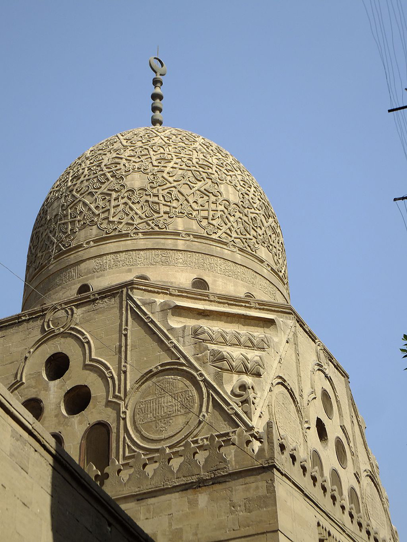 View from below of exterior of ornate stone dome atop a stone building.