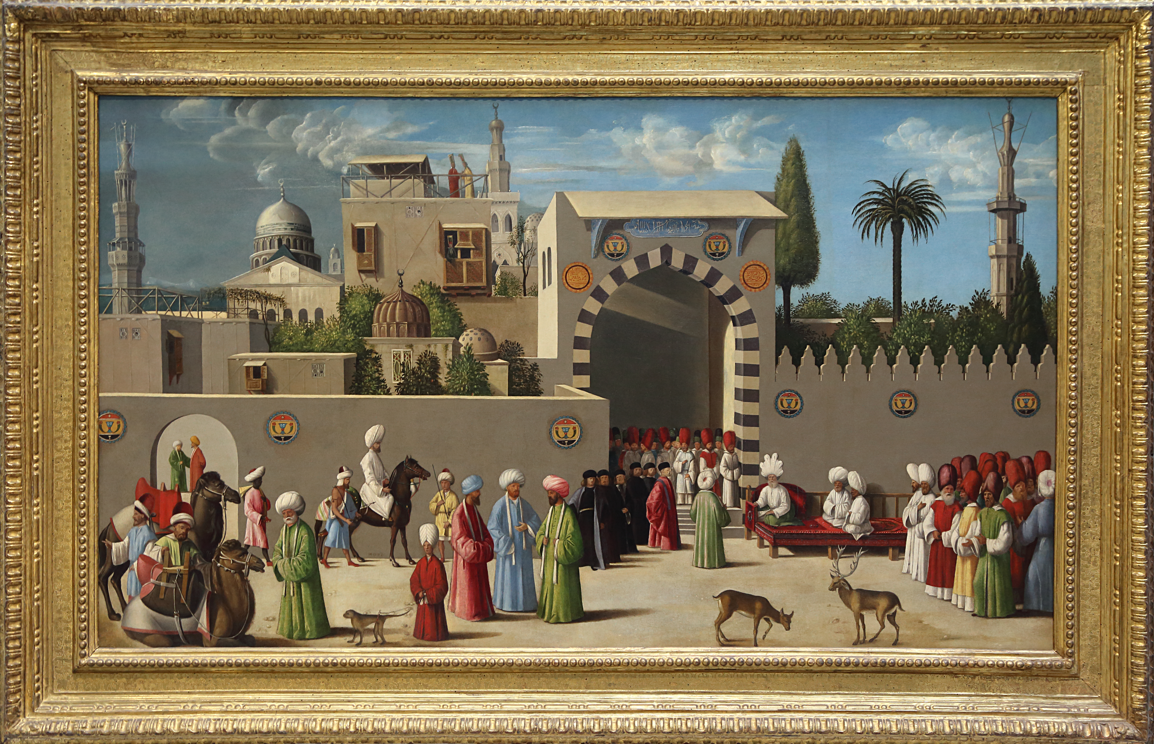 People in brightly dressed robes and turbans gather outside a low-walled city or fortress.