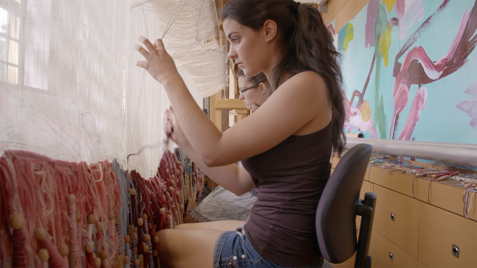 A woman in a tank top and denim shorts, sits before a large unfinished tapestry, holding threads as she weaves.