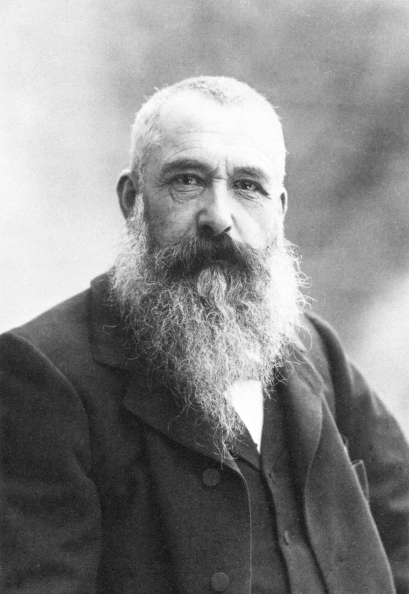 Claude Monet, with a full gray beard and close-cropped hair, wearing a dark coat over a suit jacket or vest.