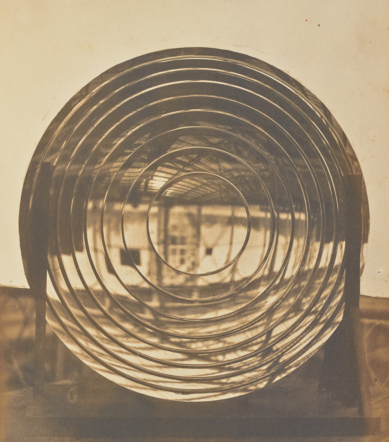 Sepia print of circular glass disc with multiple concentric circles within it.
