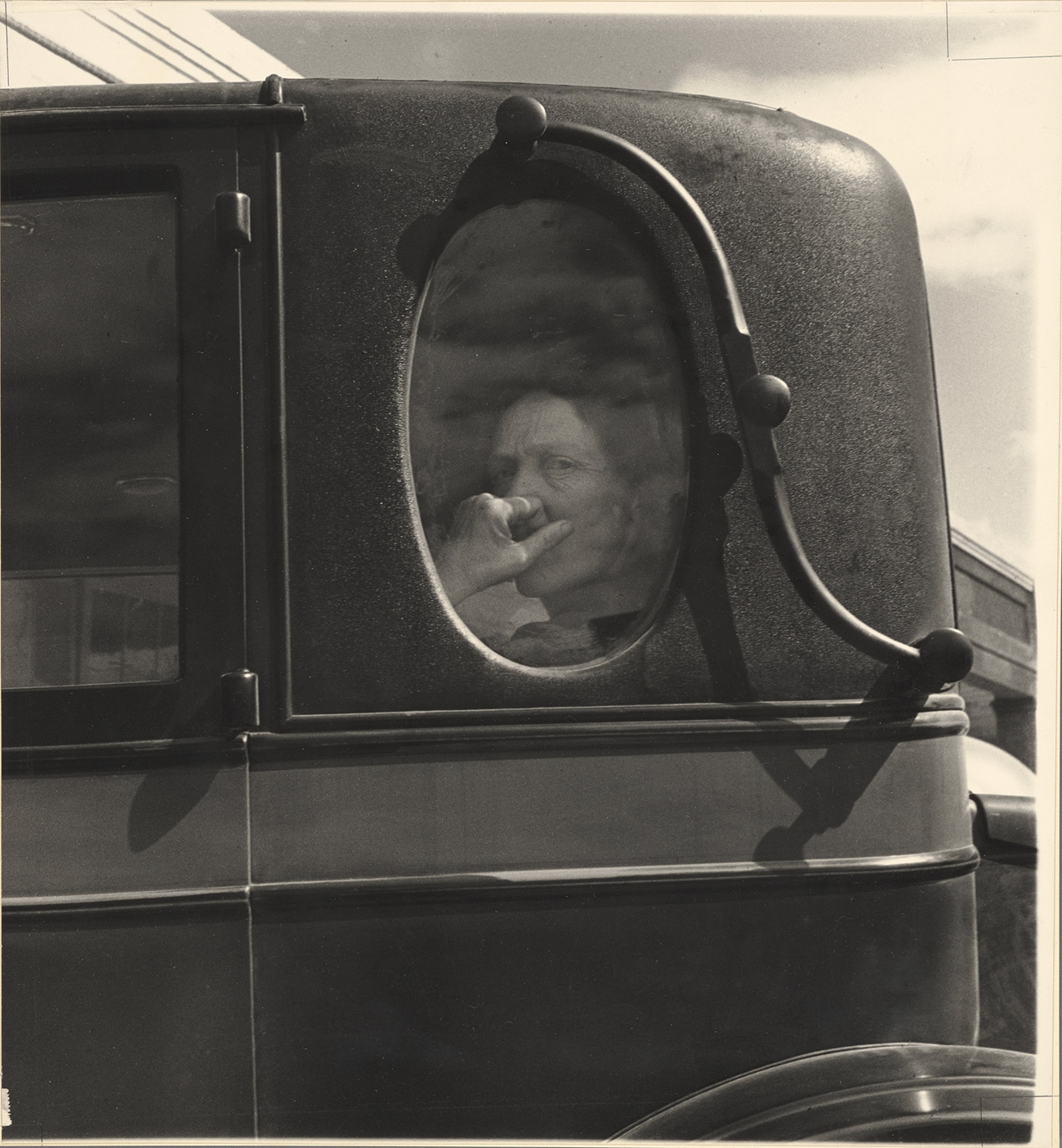 A woman holding a kerchief to her mouth looks out of the window of an old vehicle.