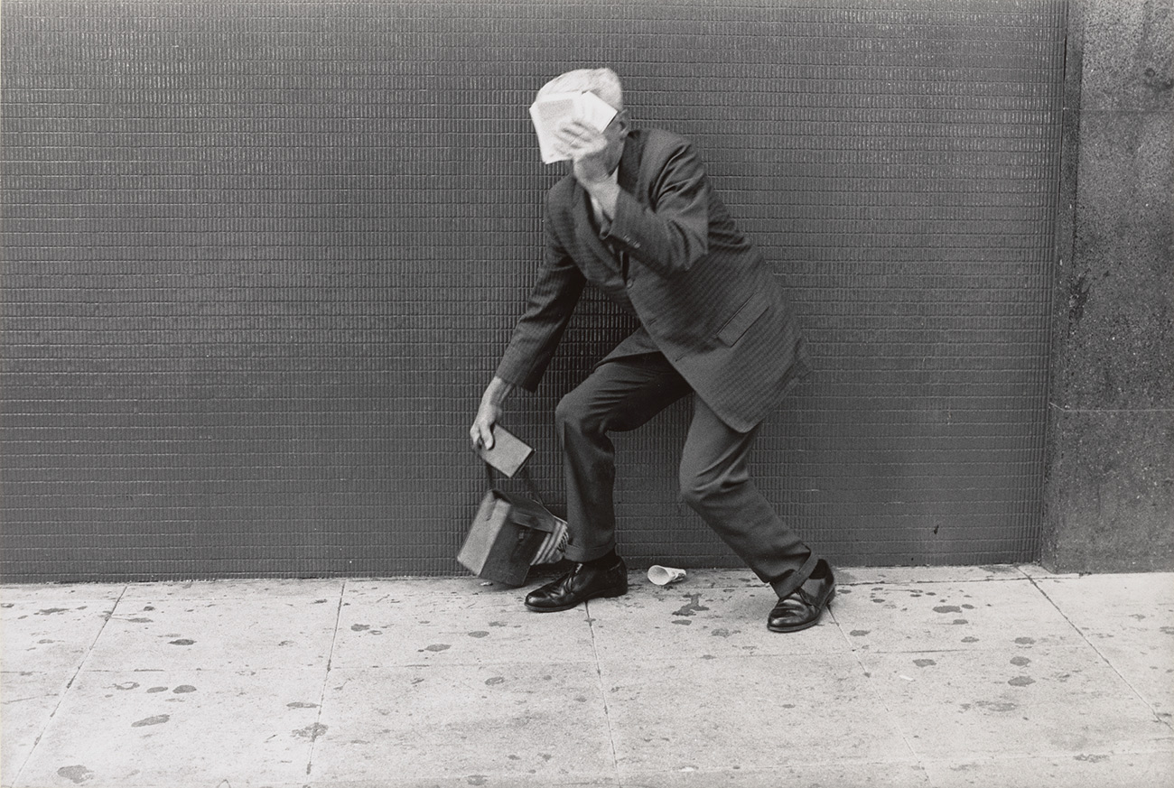 A man in a suite crouches in front of a wall, holding papers to block his face.