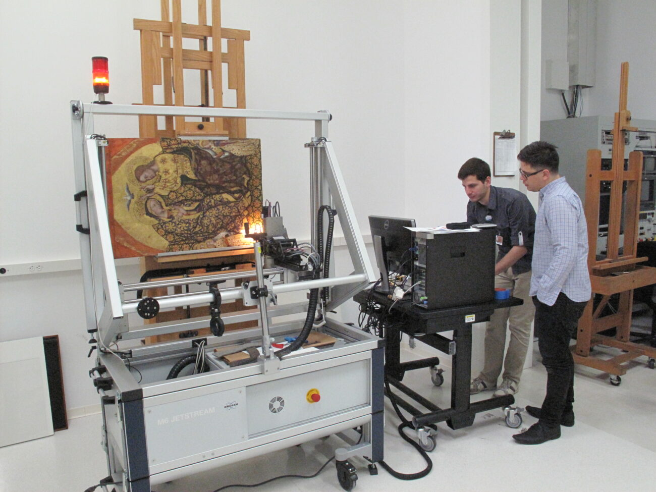 Researchers at the lab look at a painting