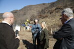 Jim Cuno, Gideon Brower, Lisa Lapin, and Steve Olsen speaking in front of a burned hillside below the Getty Center campus