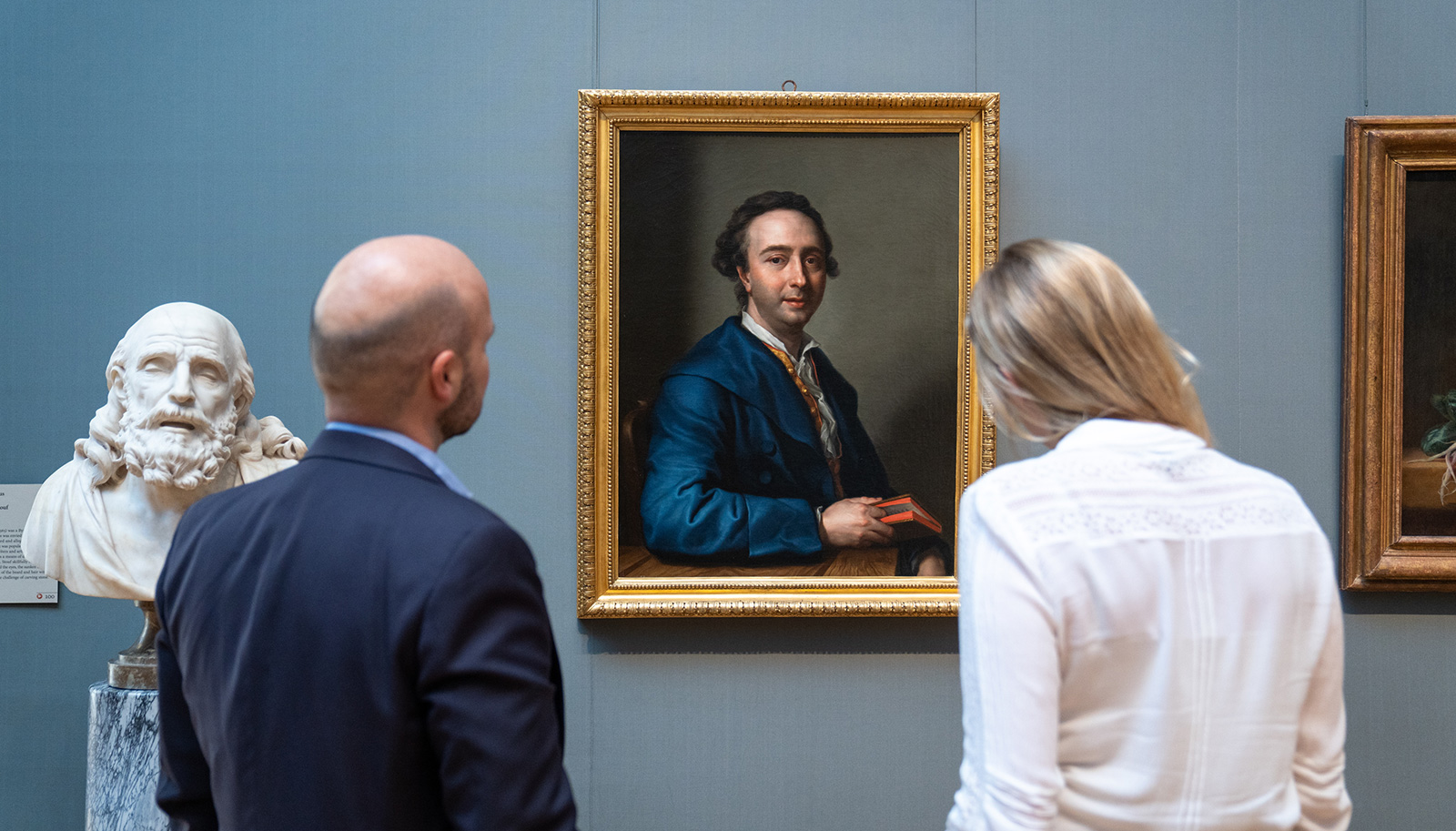 Two people looking at the new portait of a seated man in a blue coat.