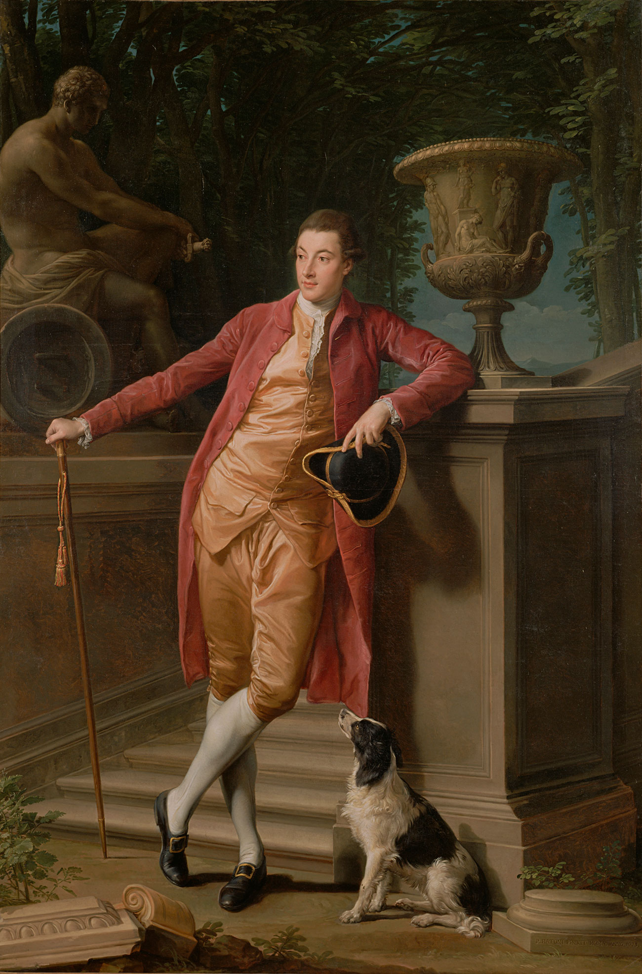 Full figure of a man in a long red coat and pink breeches leaning against a pillar and holding a tri-corner hat. A black and white dog sits at his feet.