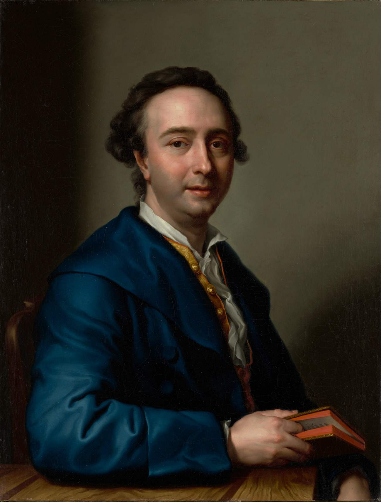 Upper body portait of a seated man with brown hair wearing a blue coat over a gold vest and white shirt or ascot. He's using his right index finger to mark is place in the book he's holding.