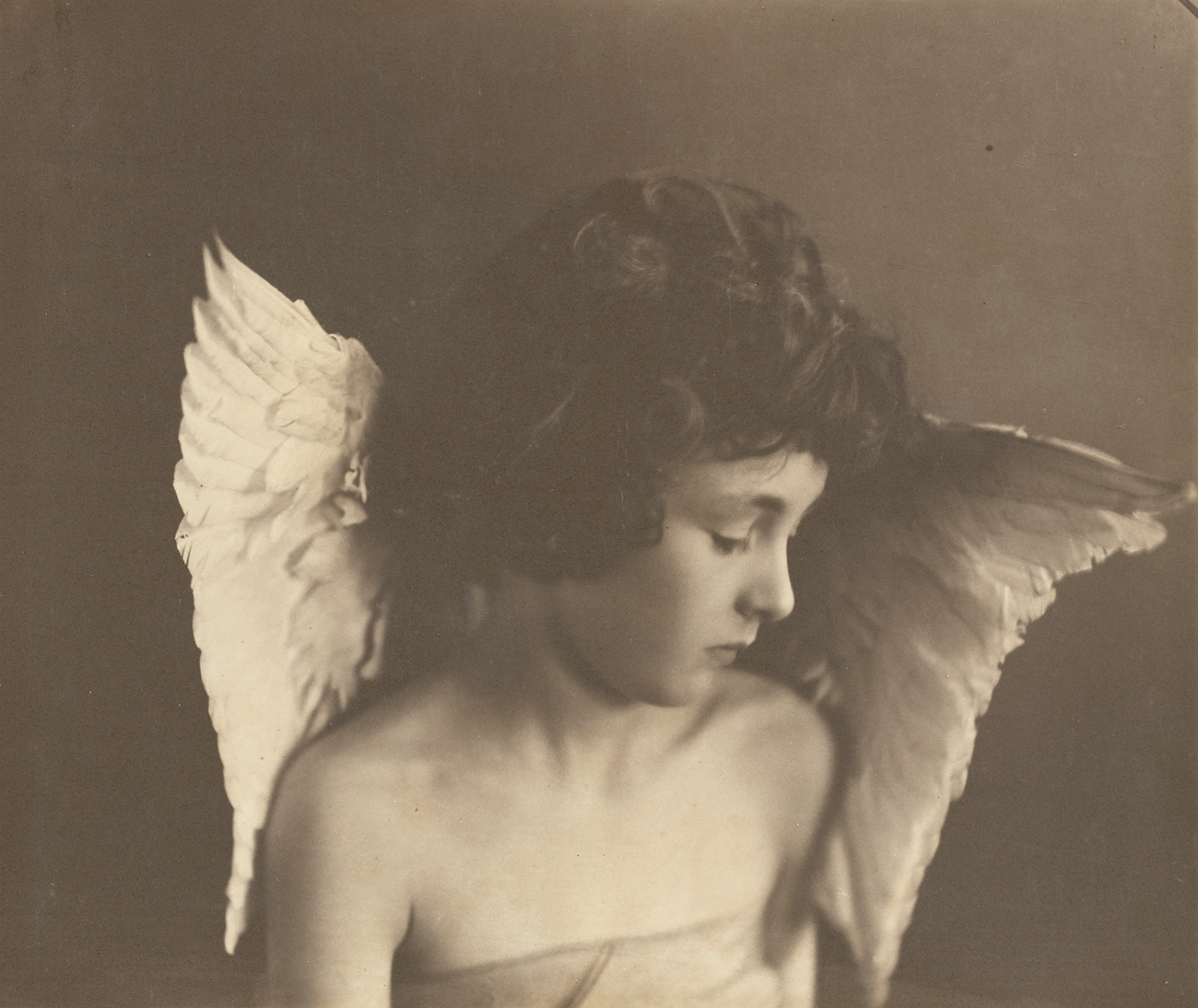 A young child with tousled hair and wings