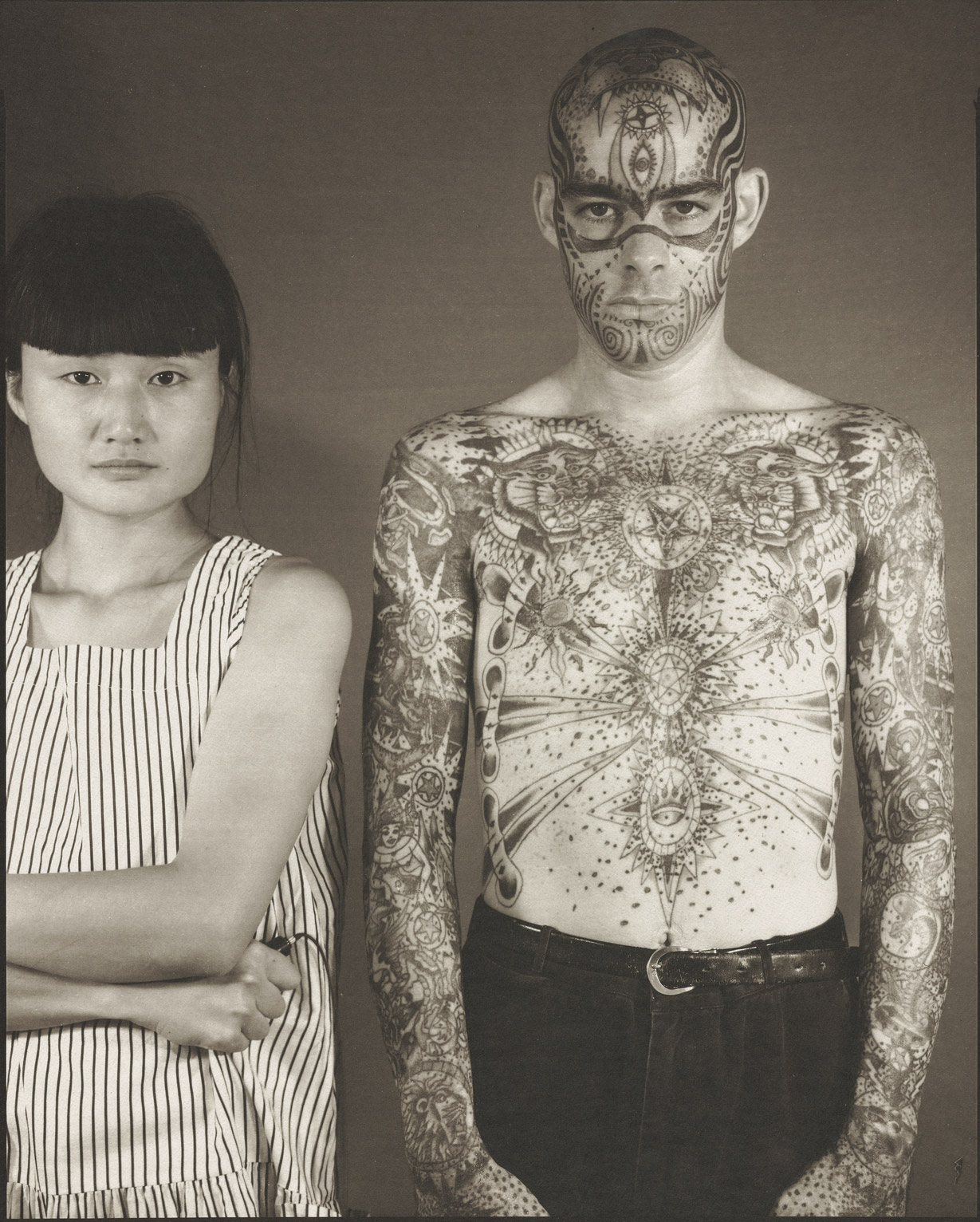 Madoka Takagi with bare-chested, tattooed Latino man