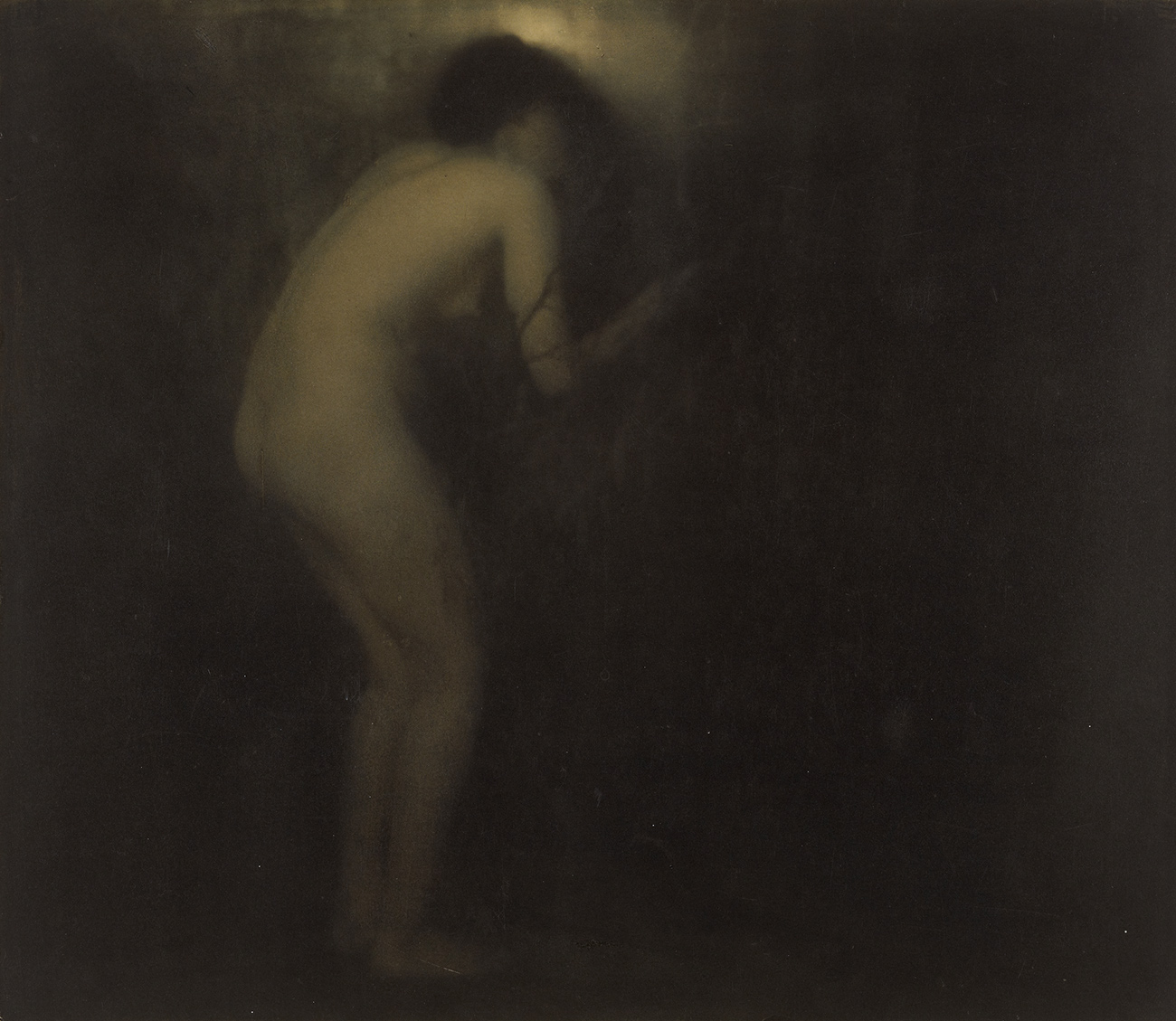 Nude woman crouches by a door or window
