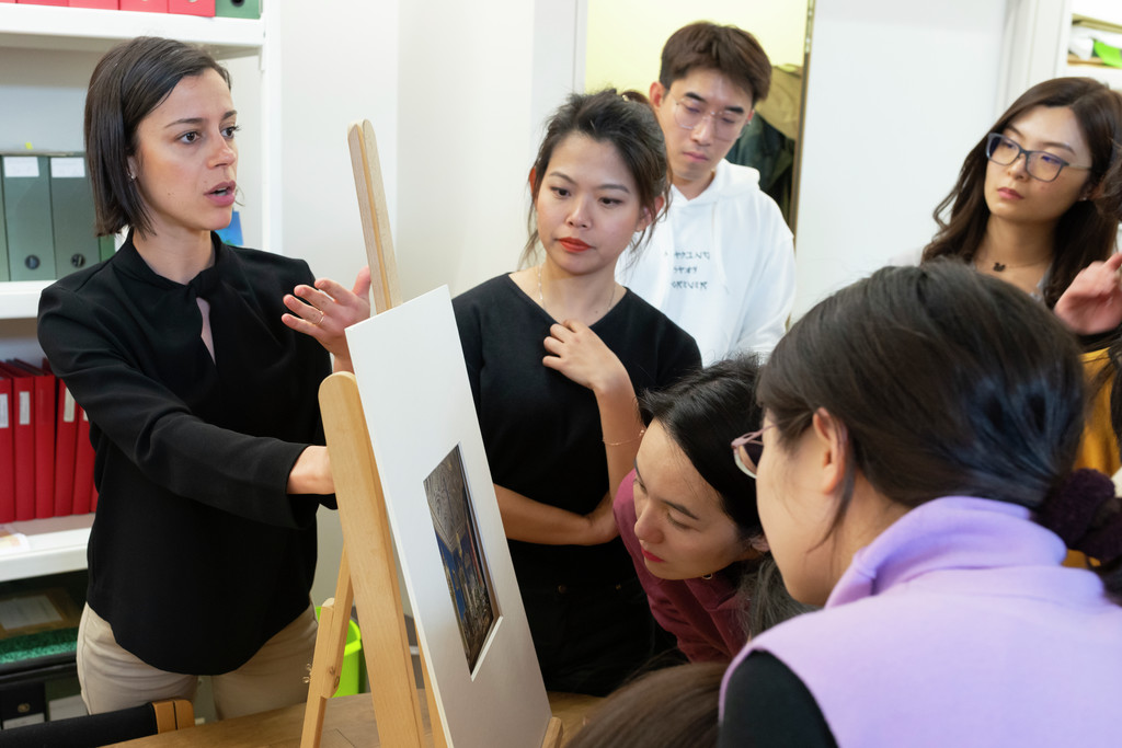 A small group of people, possibly students, look closely at something framed by a white matte.