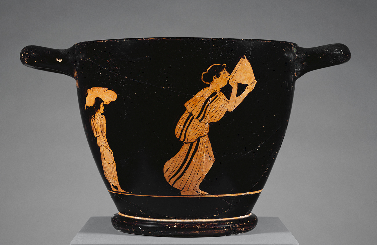 Black cup with painting of woman in toga drinking from a large cup.