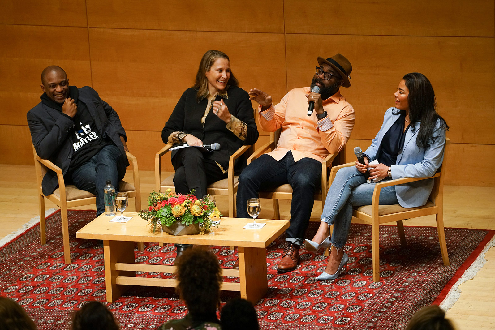 Four people sit on a stage as part of a panel discussion