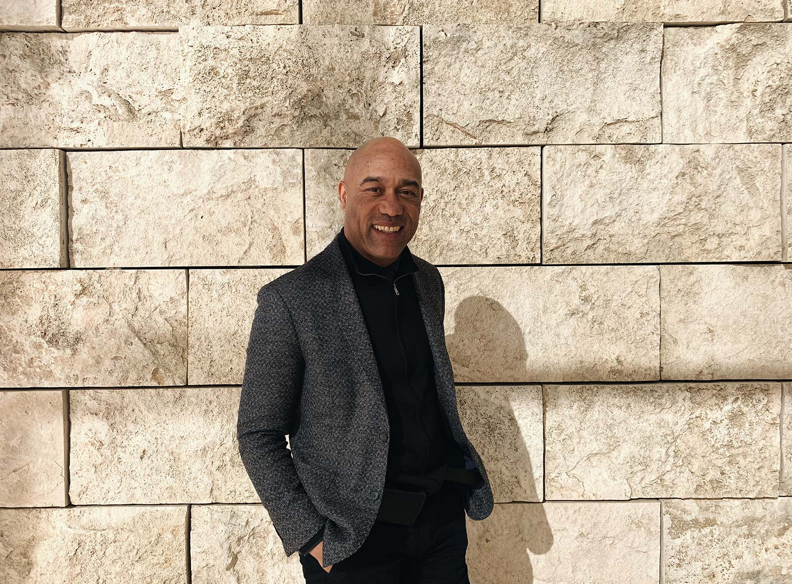 A man dressed in black with a gray blazer stands before a travertine wall