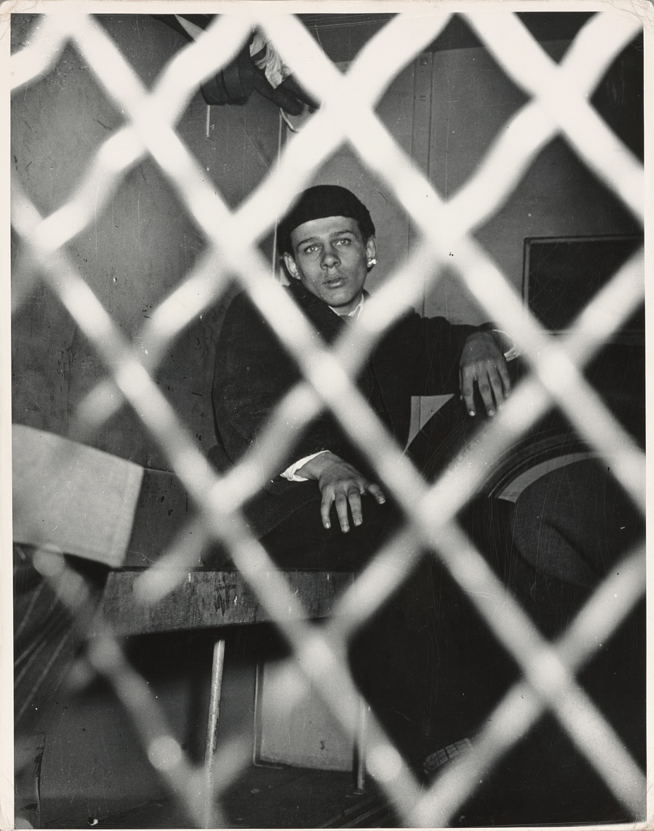 A teenage boy sits in a small room, looking at the camera from behind a chain fence