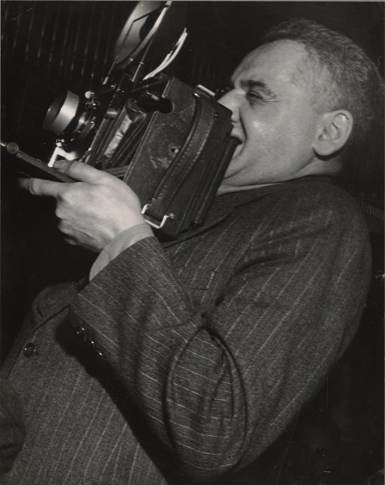 Weegee holds an old-fashioned camera up to his face, looking to the left of the viewer.