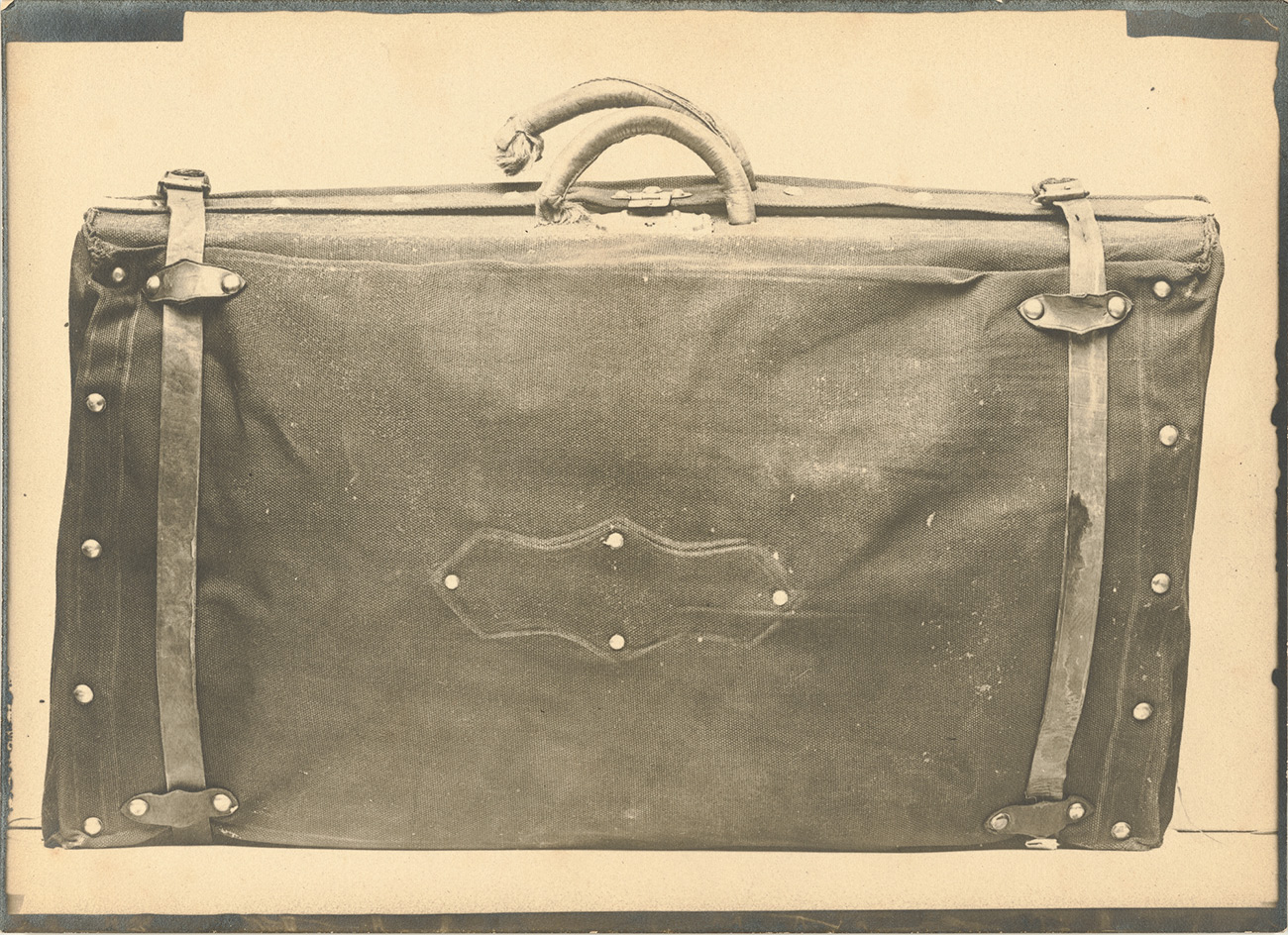Closeup of a leather suitcase with straps across each end and two handles--one broken--at the top.