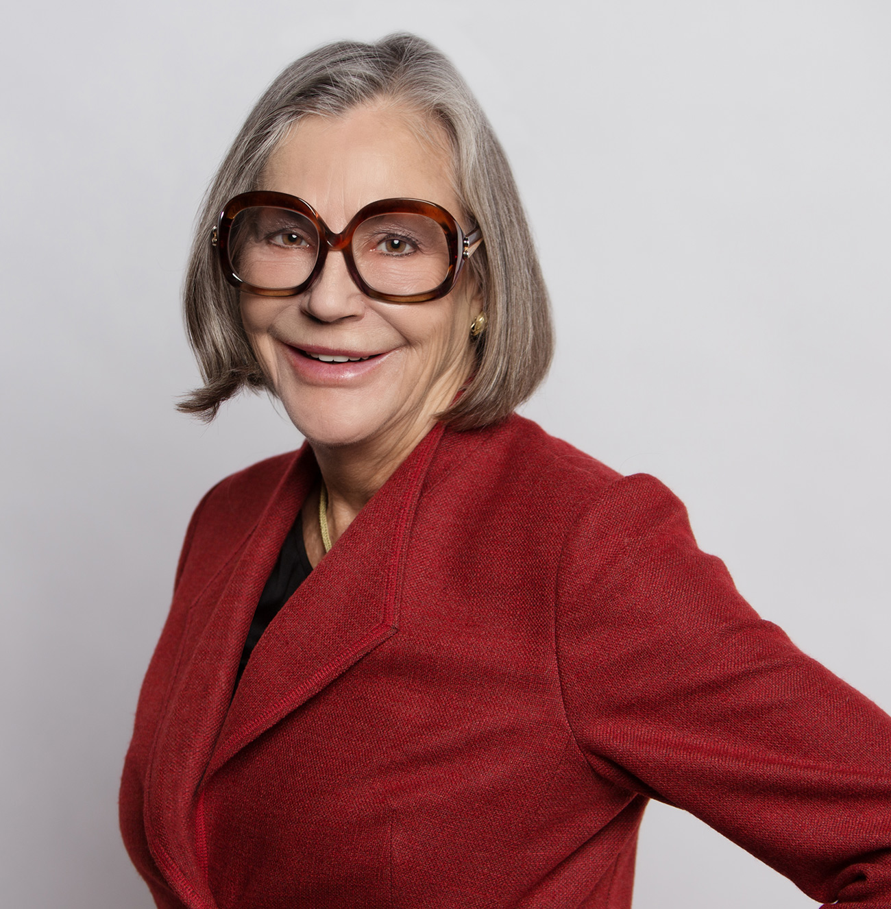 Alice Walton wears a red jacket and large-framed glasses