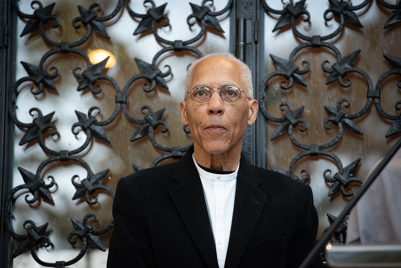 Martin Puryear stands in front of a a wrought-iron door, wearing a white shirt with a black jacket, and thin-rimmed glasses.