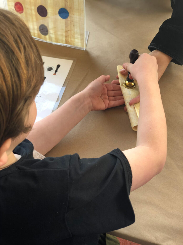 A child seals a rolled papyrus with wax.
