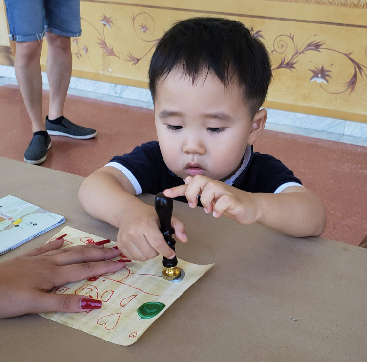 A young child presses a wax seal to paper