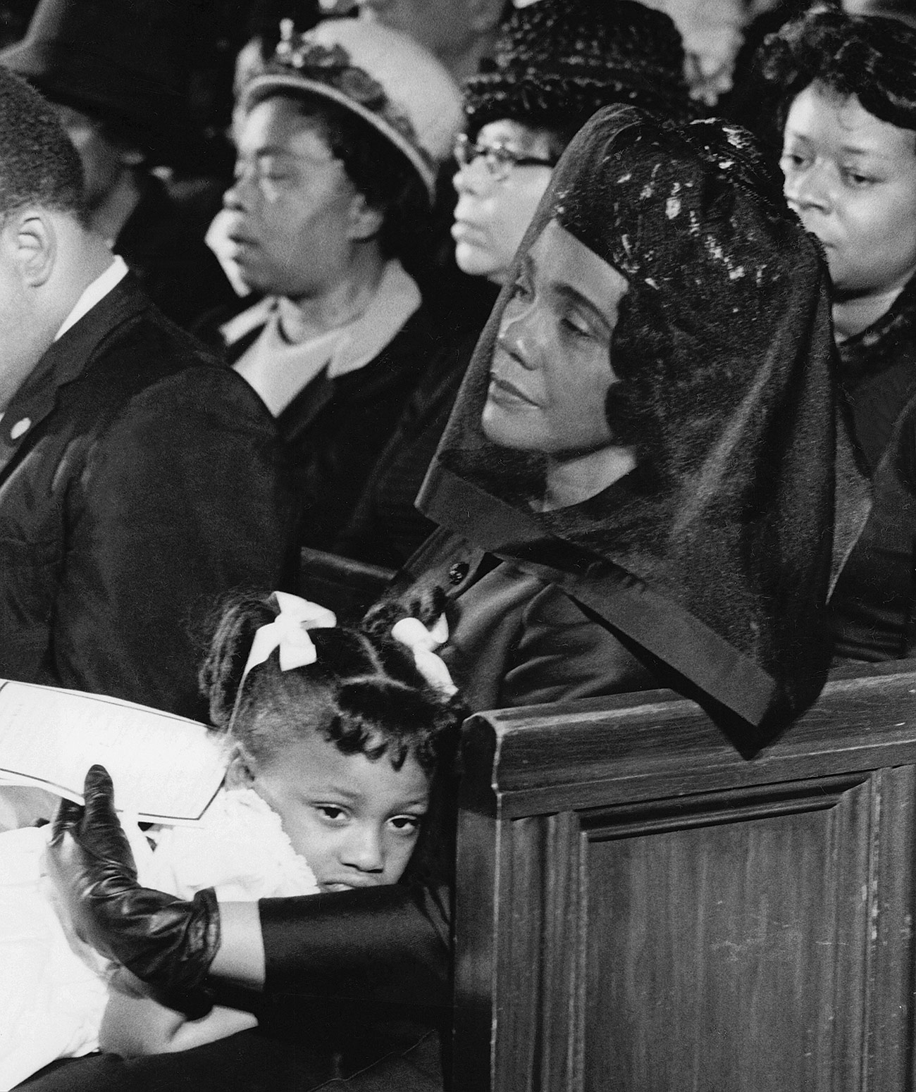 King wears a veil over her face as she sits in a pew holding her daughter, who wears white with white ribbons in her hair.