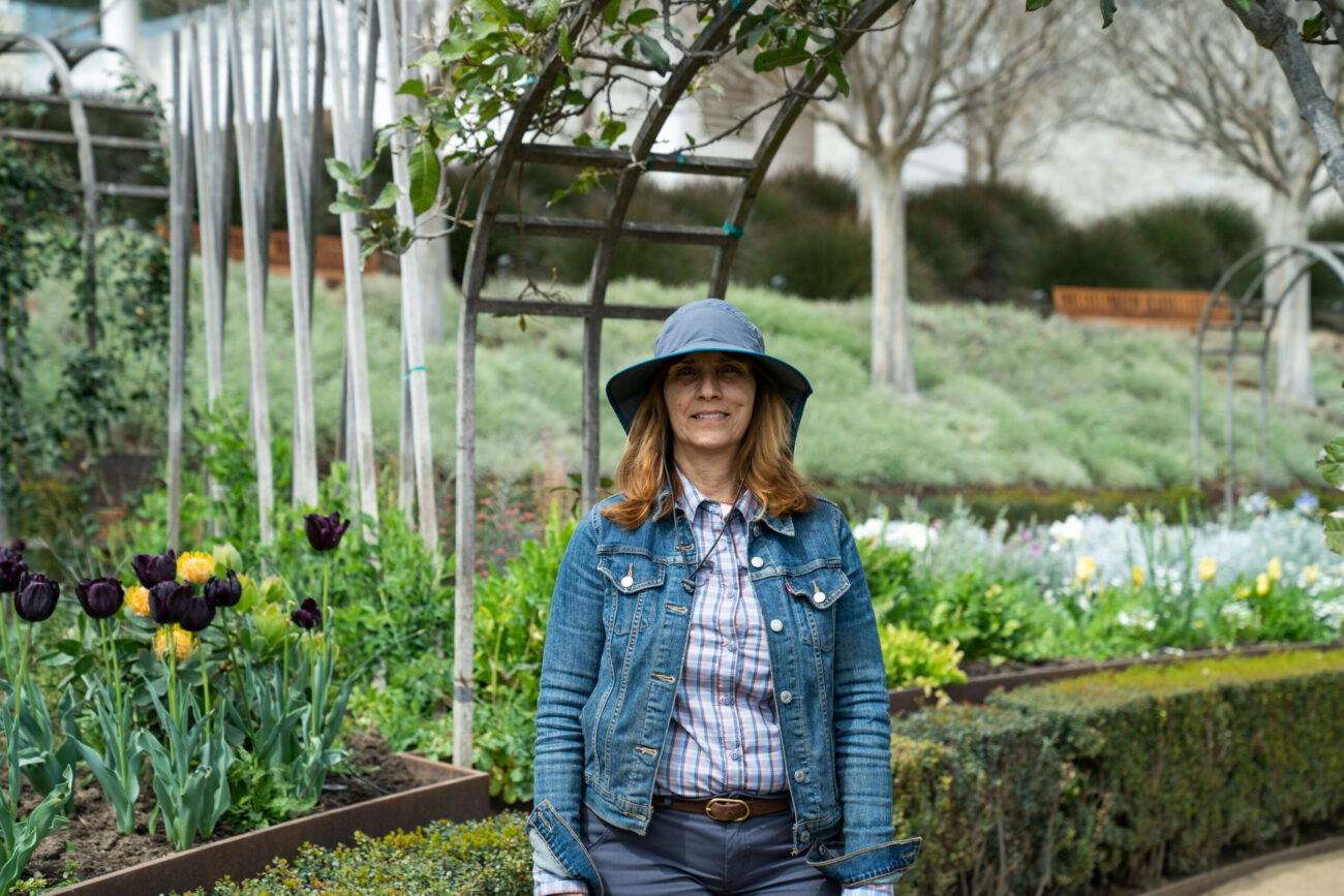 Woman in hat stands in the garden