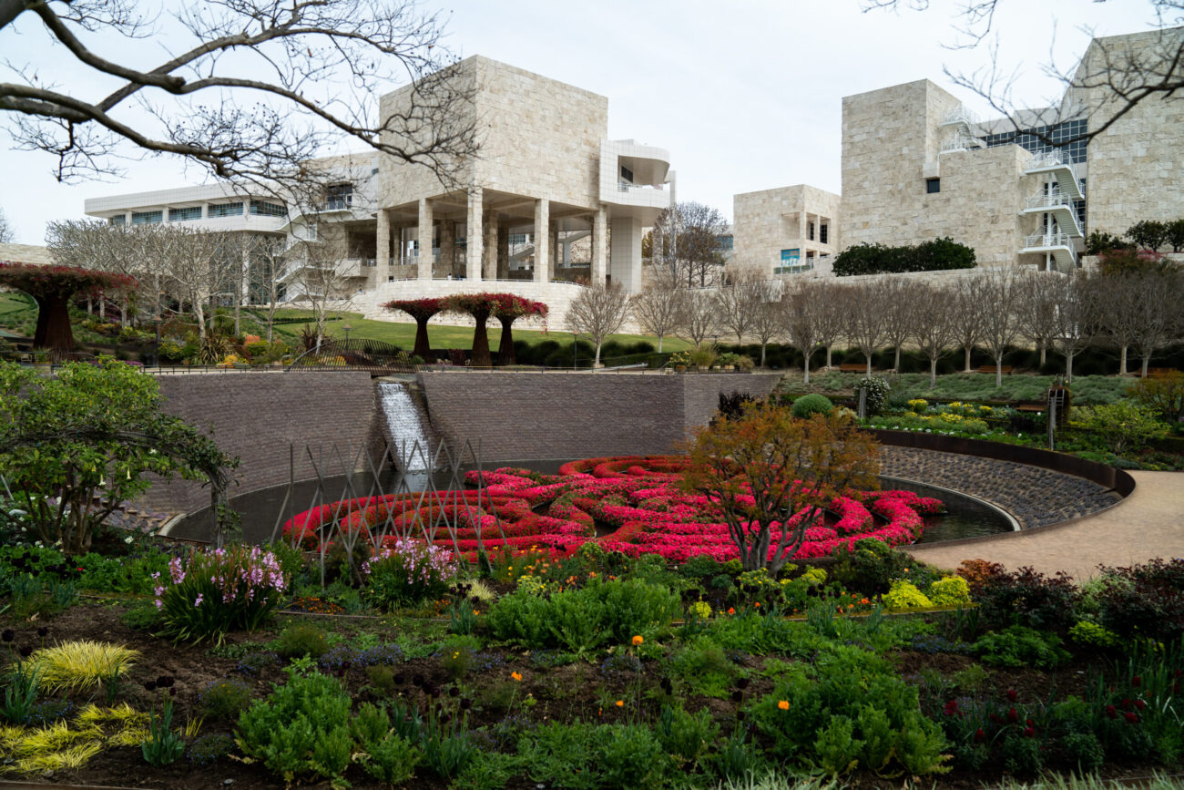 Wide-angle view of the Getty's Central Garden showing the azalea maze in full bloom and the Museum buildings towering behind