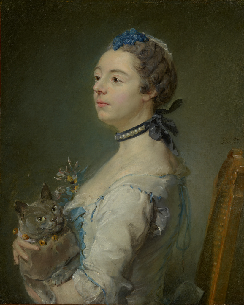 Portrait of a woman sitting facing left, holding a fluffy gray cat.
