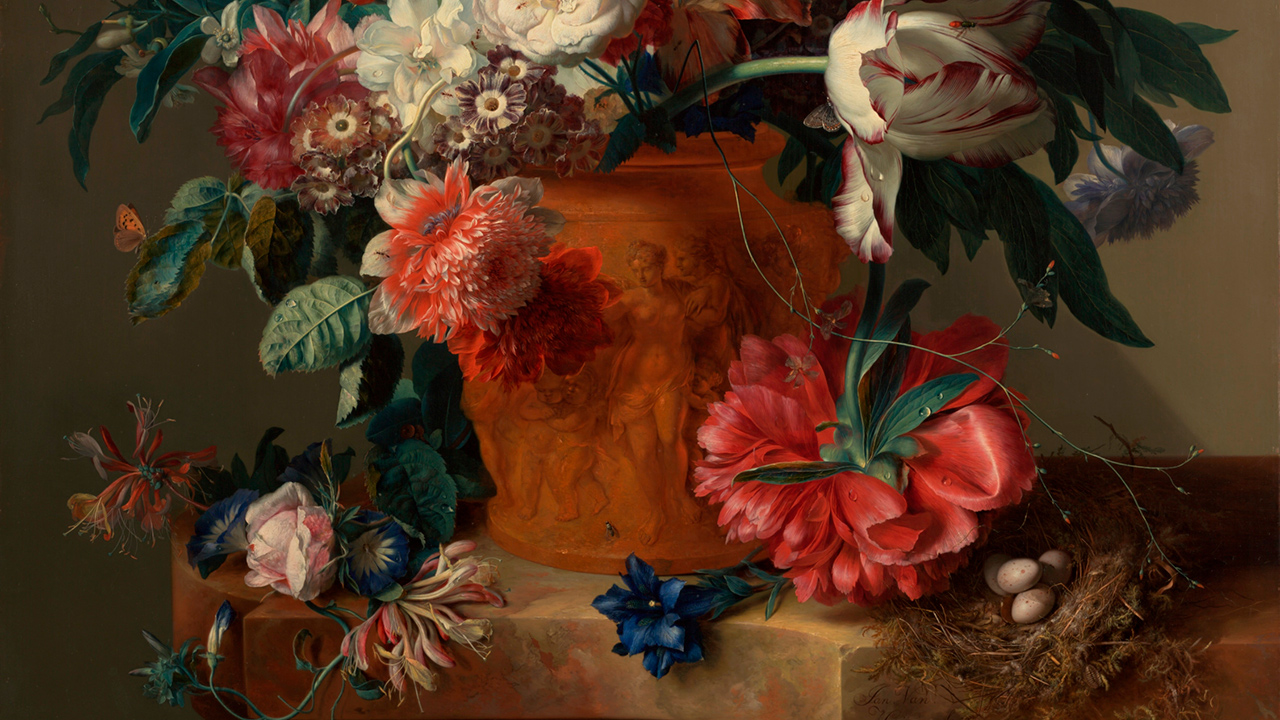 A terracotta vase embossed with classical nudes holds various types of flowers of red and white. A bird's nest with three eggs lies to the right.