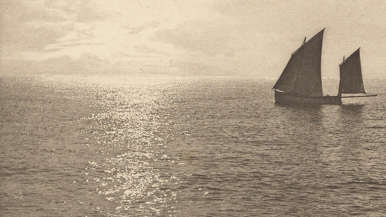 Black and white photo of two sailboats on quiet waters with the sun behind and to the left.