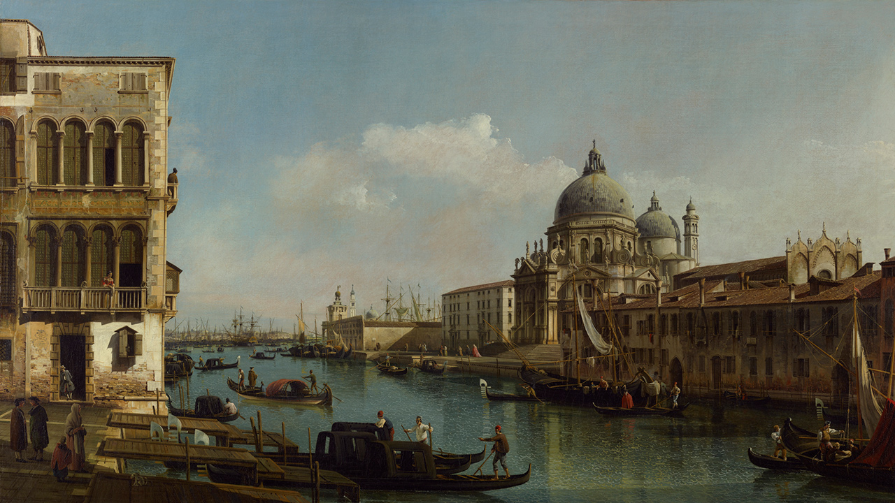 A canal with small boats, each manned by 2-3 people. A building with arched windows is on the left, and across the canal are more buildings, one with several domes on top.