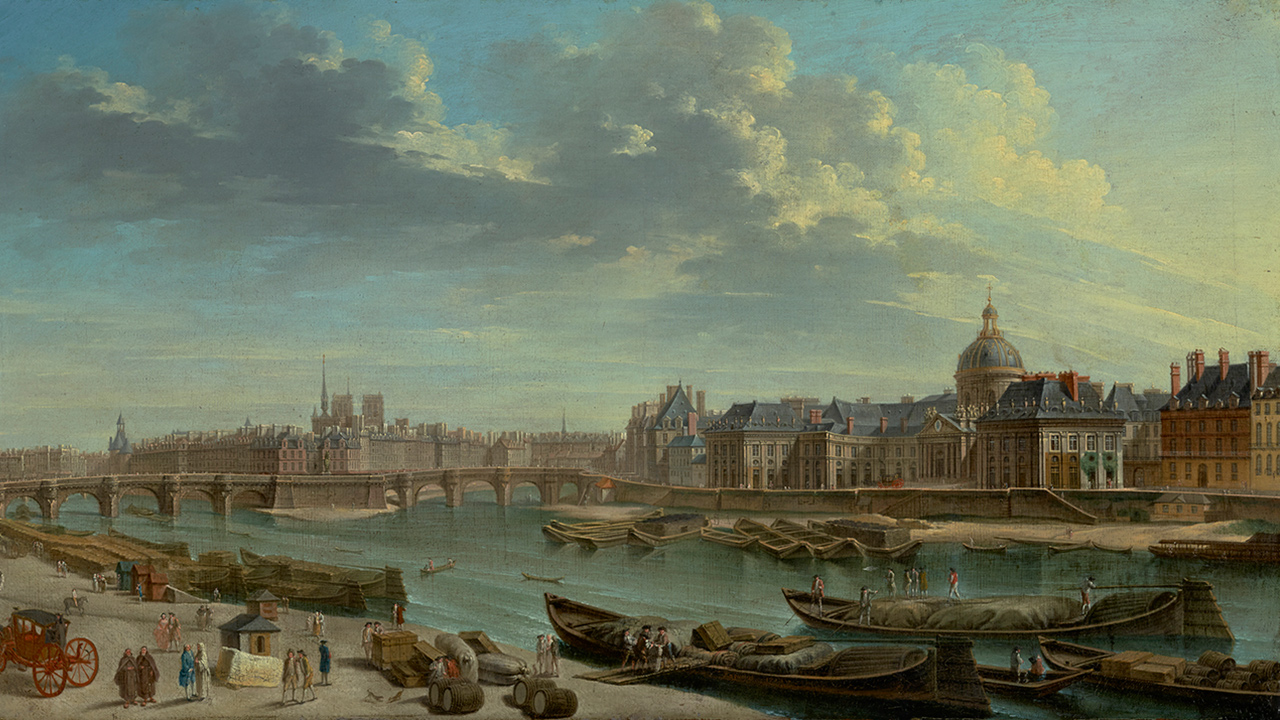 Cityscape on a cloudy day, along a river or canal. Barges are docked on the nearby sandy short as people unload their goods. Across the water are buildings, one with a large dome. A bridge spans the water in the distance.