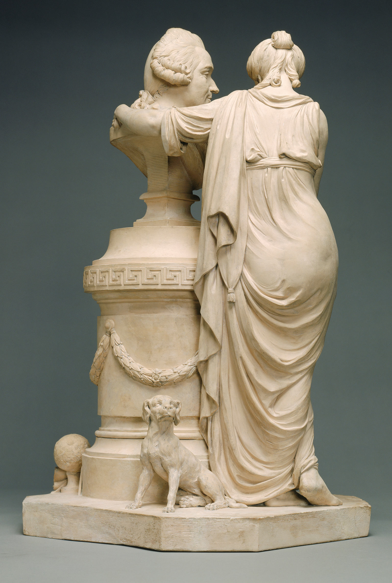 Backside of a woman in a toga standing next to the bust of a man on a tall pedestal, with a small dog standing behind them.