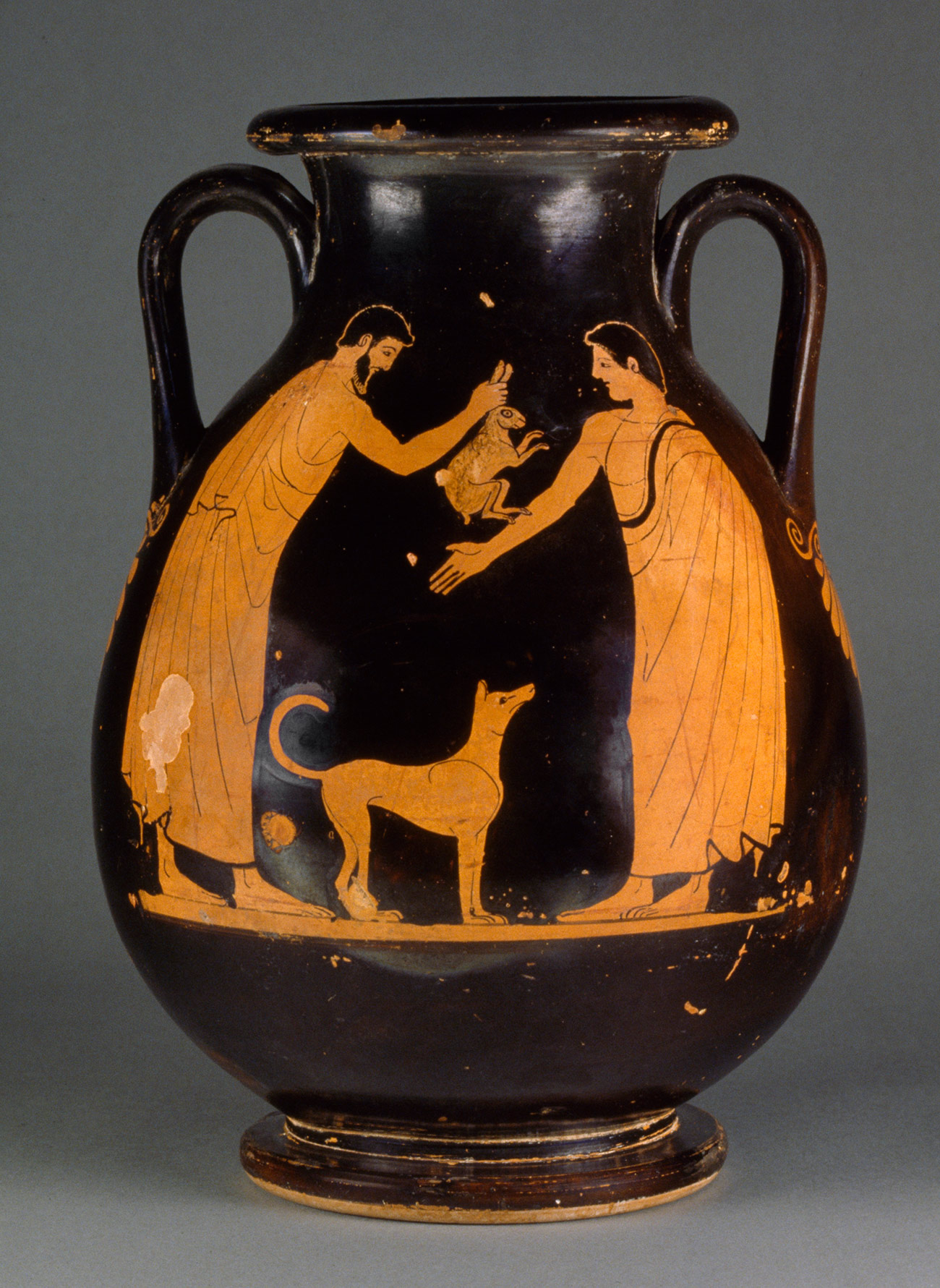 Black vase with amber-colored figures. Two men stand over a dog, one holding a rabbit by its ears.
