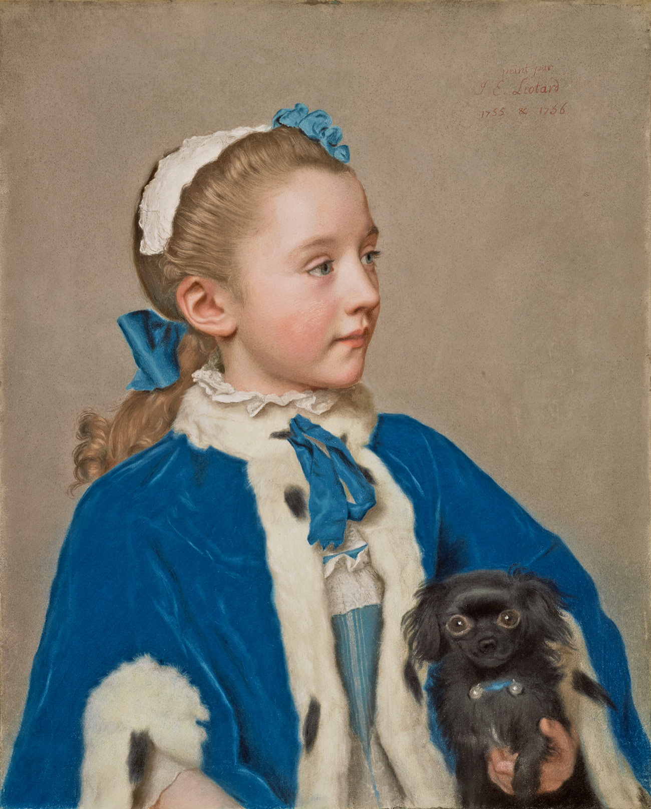 Young girl in a blue cape with white trim, holding a small black dog.