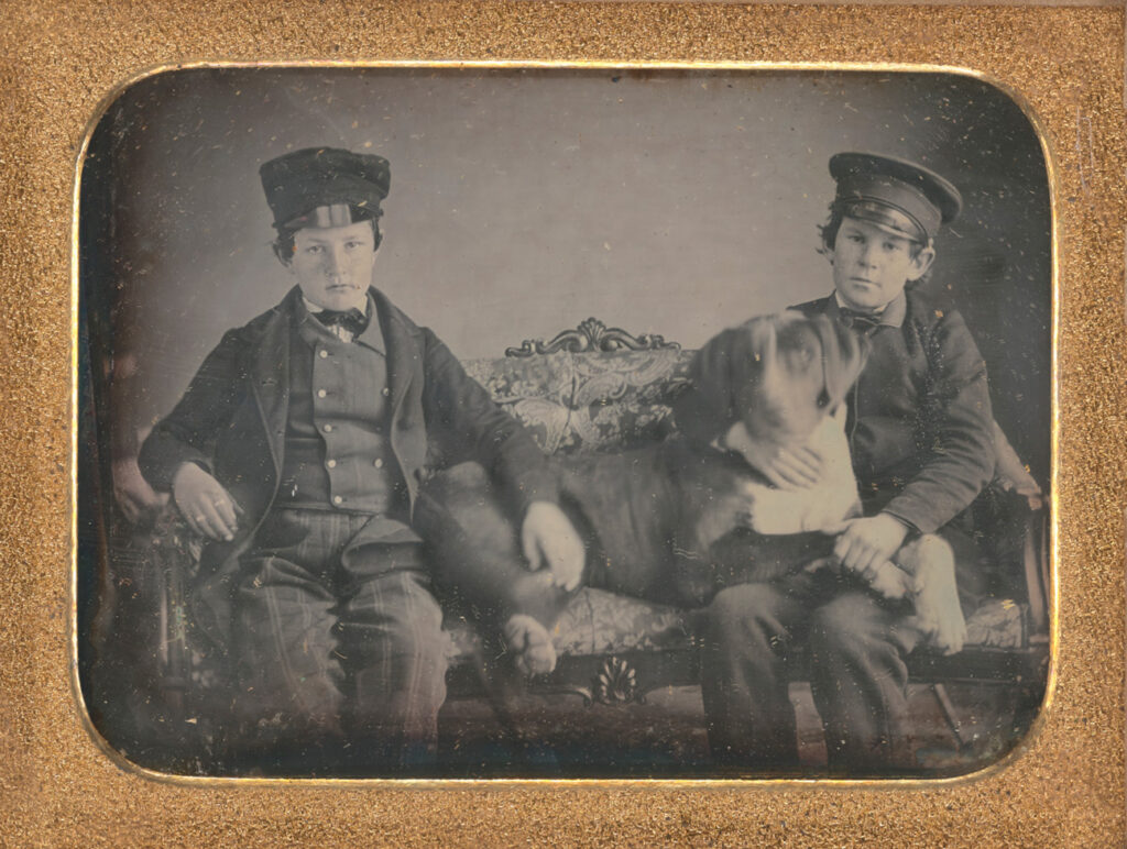 Two boys in formal attire and caps sit on a couch with a large dog looking up at the boy on the right.