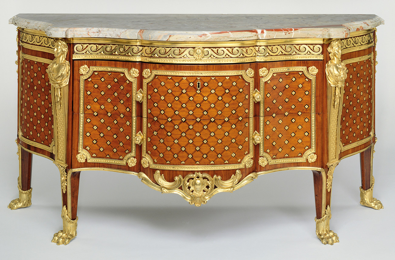 Four-legged wooden cabinet. Inlays are golden, while the top appears marbled.