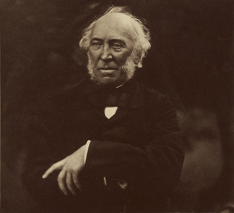 Photo of a man with thinning hair and white sideburns in a black jacket and tie