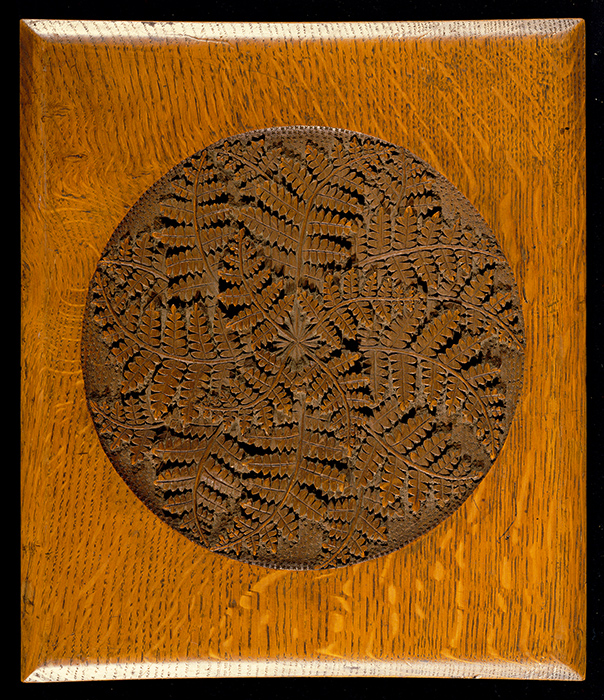 Wooden album cover with intricate leaf design in the center