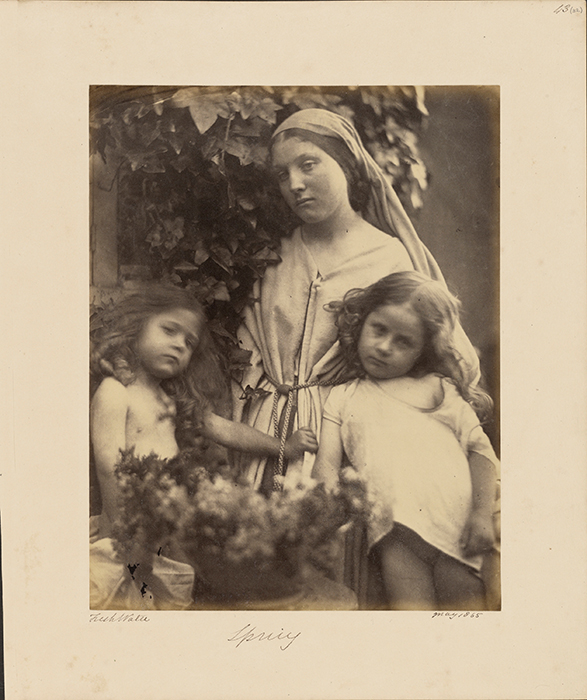 A robed and veiled woman with two young children.