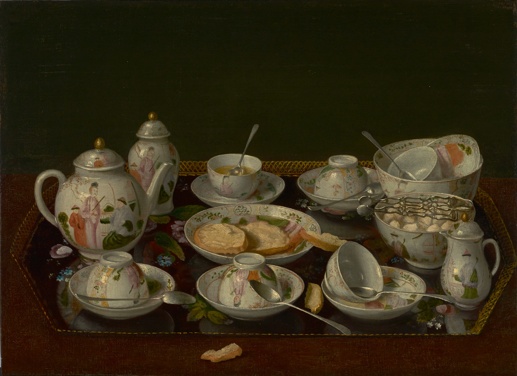 Closeup of a tray filled with a full tea set, after tea. Six tea cups--three up-ended, one half full, one lying on its side, and one in a bowl with a dirty dish. One teapot painted with an Asian woman and two Asian men; one creamer; and one other tall container. One bowl of sugar cubes, and one plate with half-eaten buttered toast.