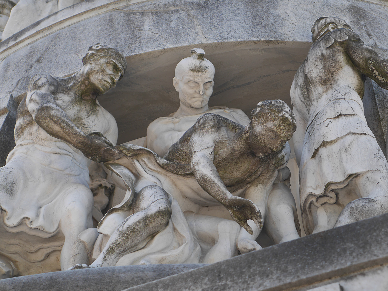 Architectural detail of four figures, one of whom is falling while either being pushed down or caught by two others.
